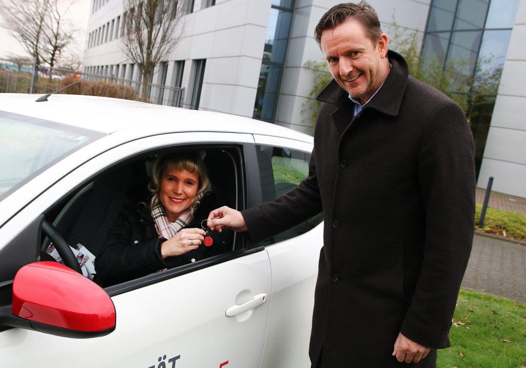 Axel Nordieker, Geschäftsführer der Toyota Kreditbank, übergibt den Fahrzeugschlüssel an Stephanie Knopf-Asselborn, Mitarbeiterin des Kölner Kreidekreises.
